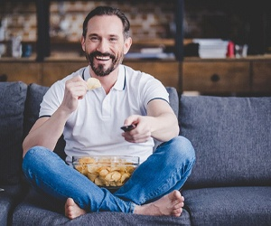 person eating potato chips on the couch