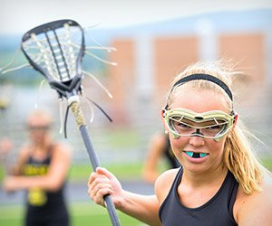 Teen girl playing lacrosse with blue sportsguard