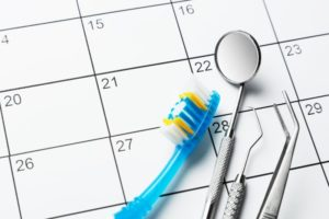 toothbrush and other dental tools resting on calendar